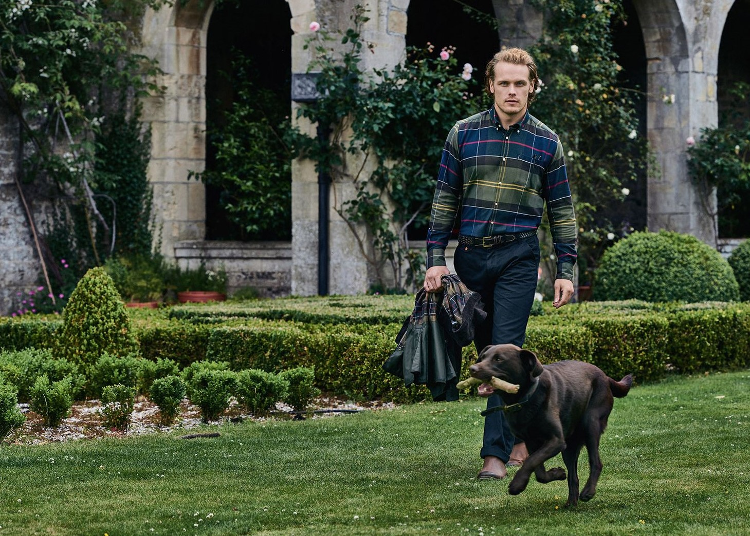 Barbour Sam Heughan wearing green tartan shirt with chocolate labrador