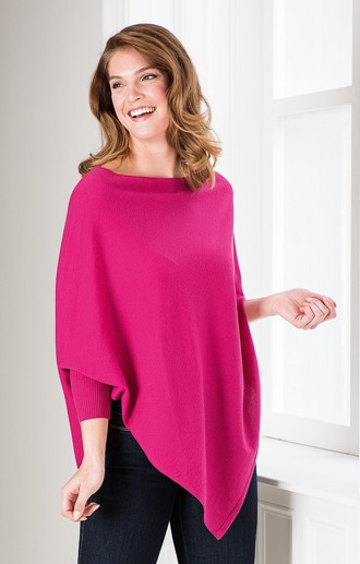smiling model in bright pink merino poncho