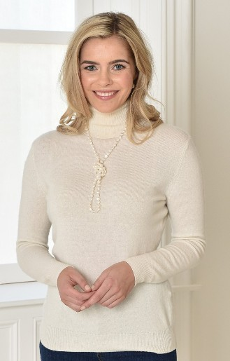 blonde model in cashmere roll neck cream with string of pearls