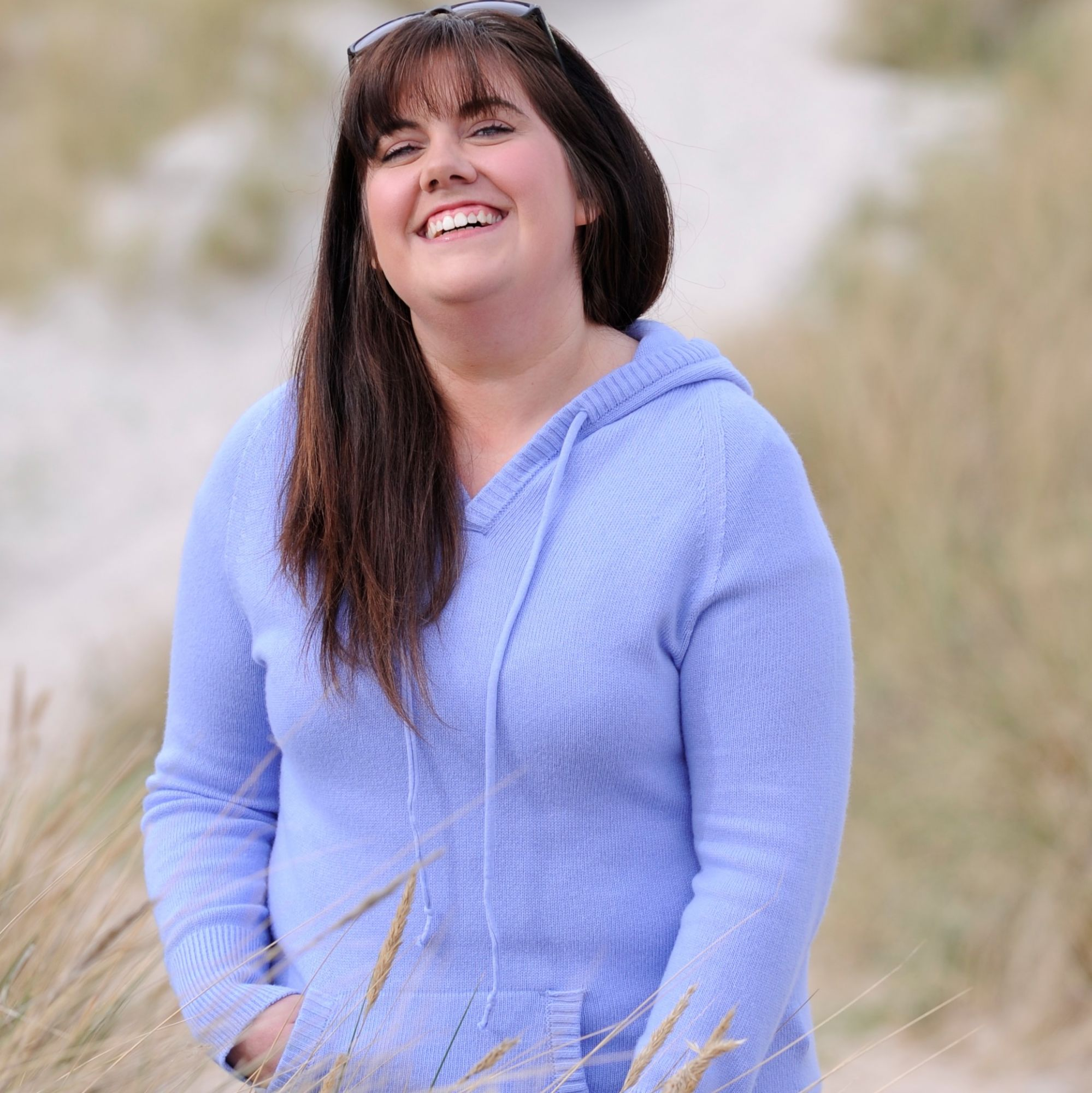 buyer wearing cashmere hooded top in sand beach