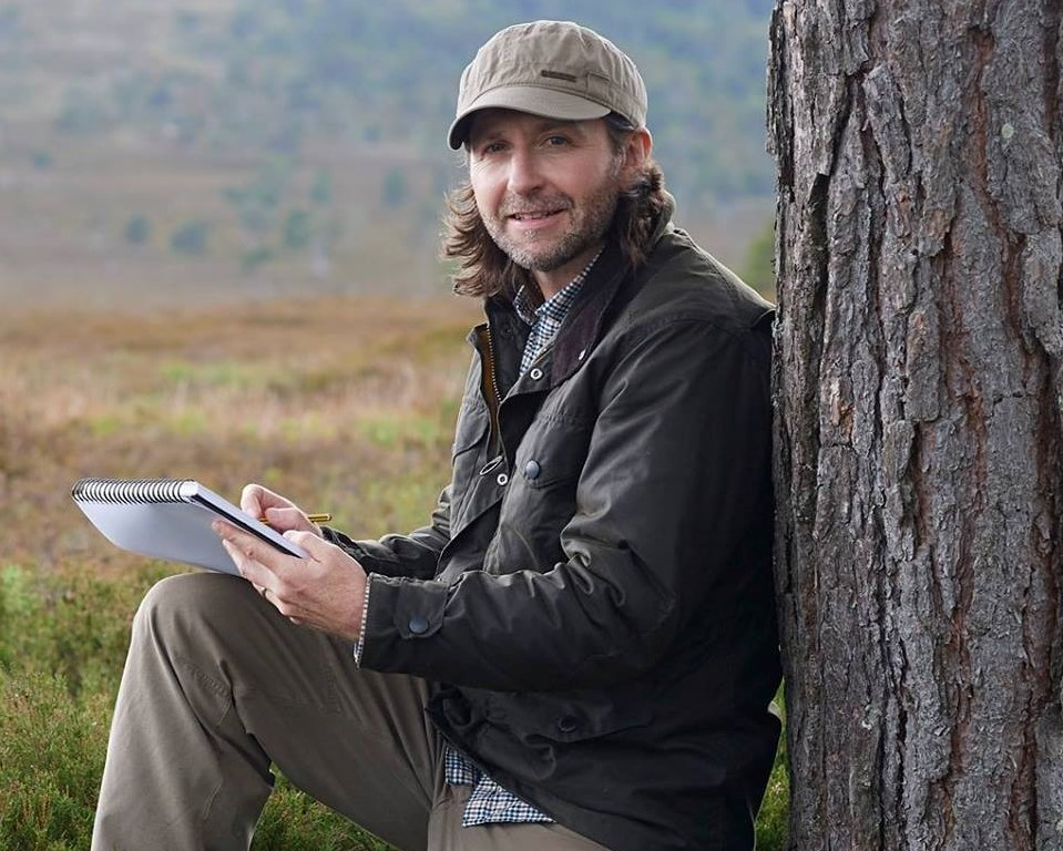 Justin Prigmore sketching beside tree