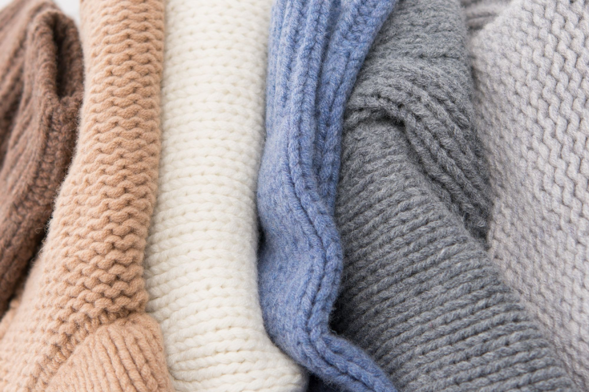 Stack of lambswool chunky knitwear in range of neutral colours