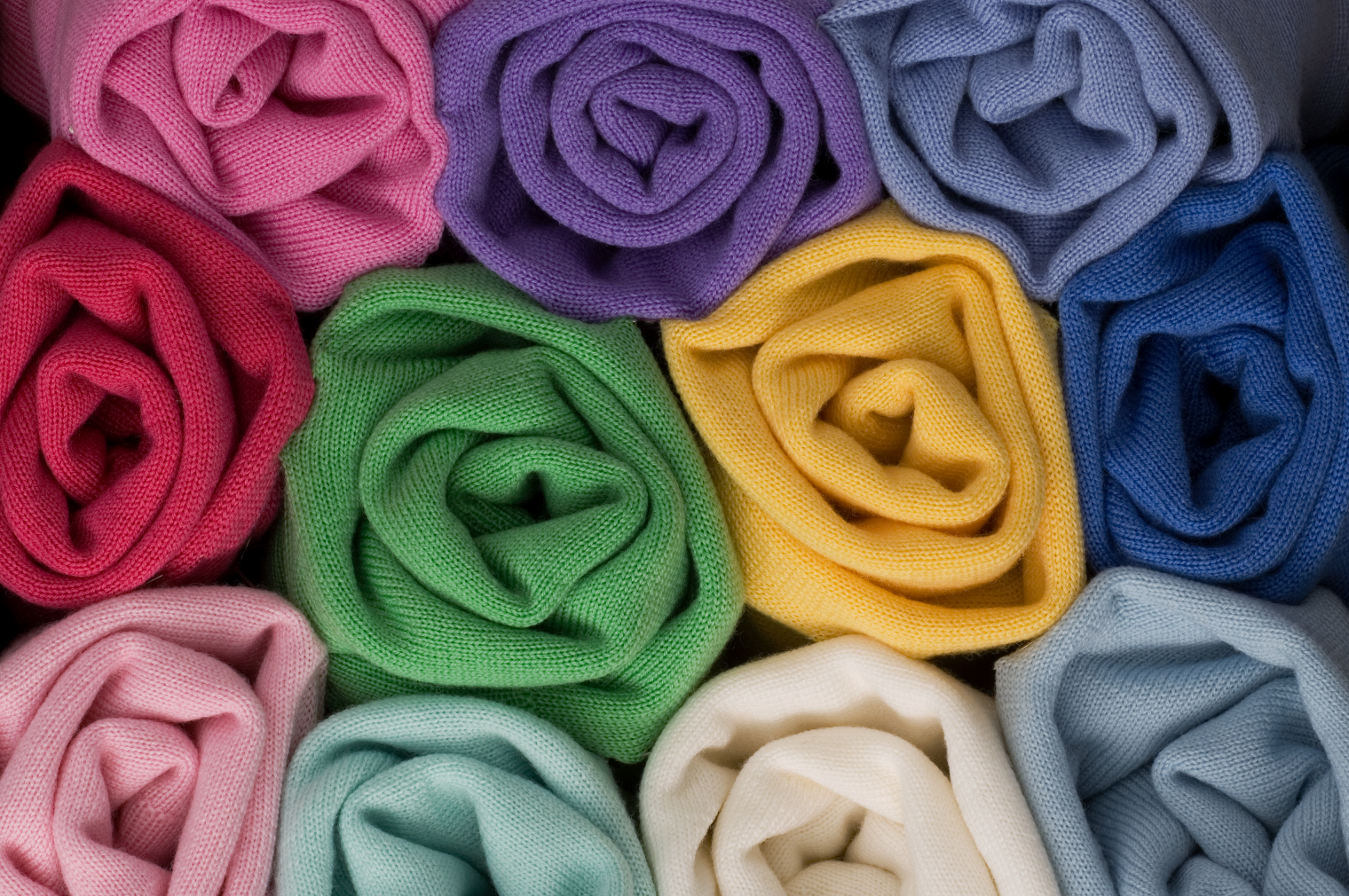 Rolls of Merino in rainbow of colours stacked on top of each other